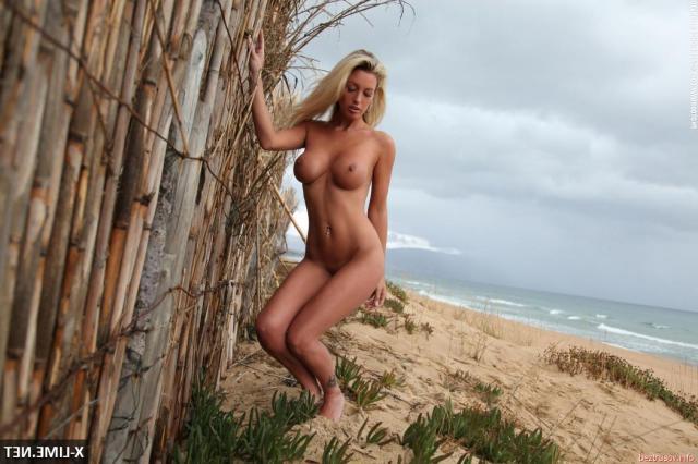 Позирование в бикини у моря взрослой девы с голой грудью