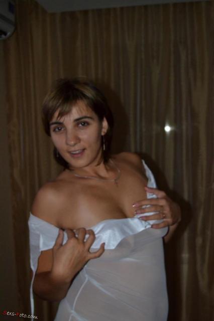 Женщина эротично позирует, делает минет и трахается между грудей