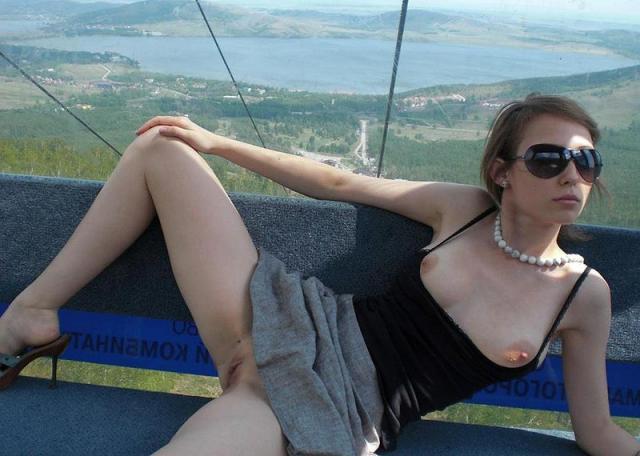 Сексуальная красотка эротично позирует голая на улице