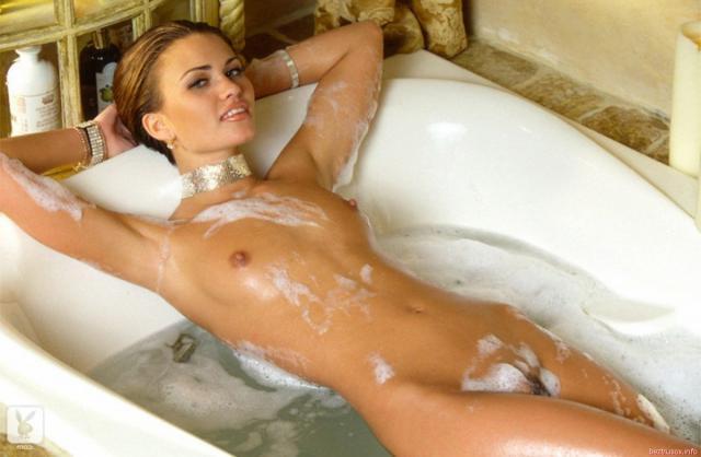 Красивая молодая девушка эротично позирует в ванной в пене