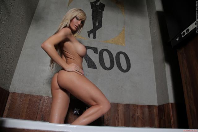 Блондинка в латексном купальнике демонстрирует пизду и силиконовые сиськи в ванной