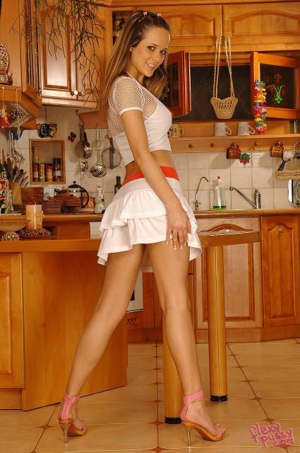На кухне молодая сексапильная студентка показывает пизду под юбкой