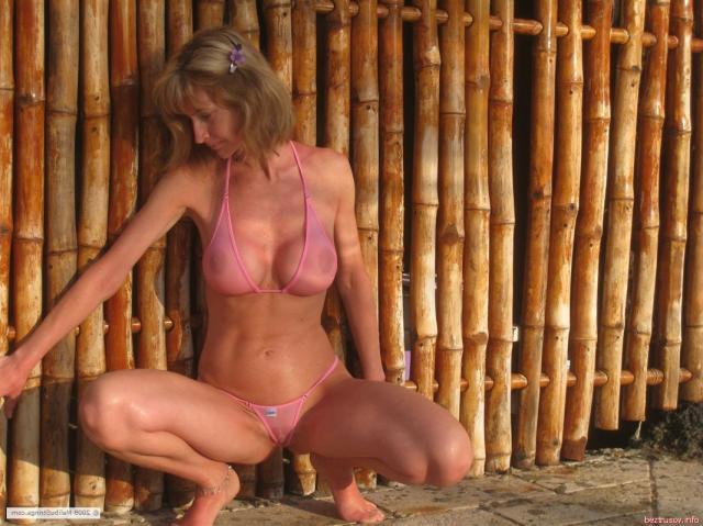 Мокрая зрелая баба в стрингах страстно позирует у бассейна