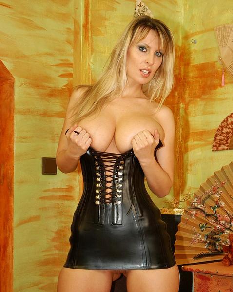 Грудастая блондинка эротично позирует в корсете, показывая писю