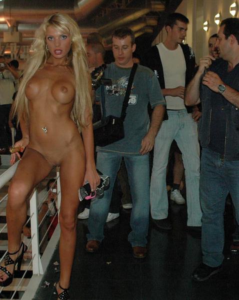 В общественных местах шлюха без одежды сексуально позирует
