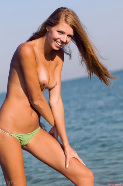 Высокая худая девушка дня бегает голой по пляжу